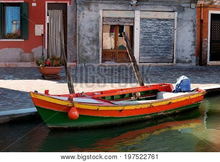 Old motorboat on the street in Burano, Italy