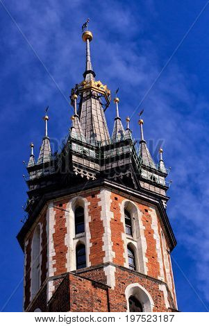 Church of St. Mary in the main Market Square on the background of dramatic sky. Basilica Mariacka. Krakow. Poland. Facade details
