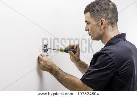 Hvac technician performing installation on a digital thermostat