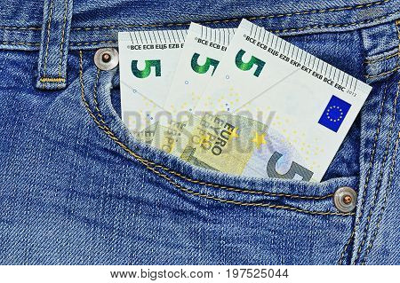Three small euro notes in front blue jeans pocket close up capture