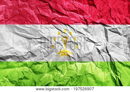 Tajikistan flag painted on crumpled paper background