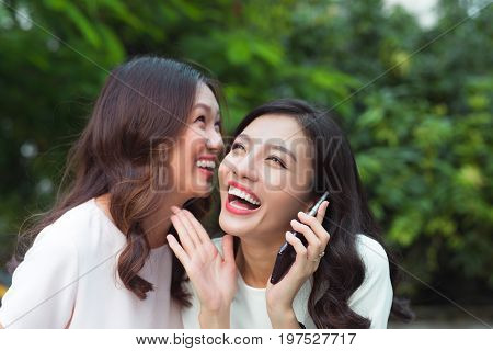 Young asian woman whispering secret into a friends ear while shes on call