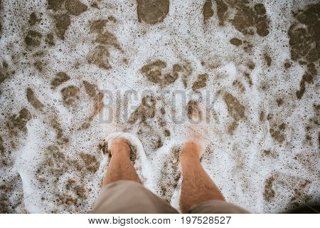 Bare feet on the beach covered with sea foam