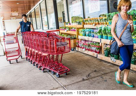 Fairfax USA - January 18 2017: Happy Trader Joe's employee returning shopping carts to the store outside entrance with woman customer