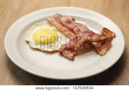 fried egg with crispy bacon stripes on plate, on wood table
