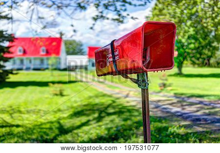 Ile D'Orleans Canada - June 1 2017: Red painted roof house with road in summer landscape French countryside with closeup of mailbox