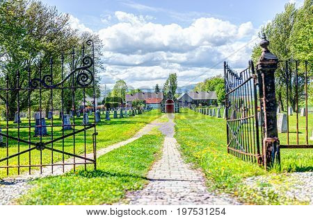 Ile D'Orleans Canada - June 1 2017: Red painted church chapel in cemetery with gate and gravestones in summer