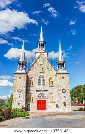 Ile D'Orleans Canada - June 1 2017: Sainte-Famille red painted church with stone architecture and blue sky in summer
