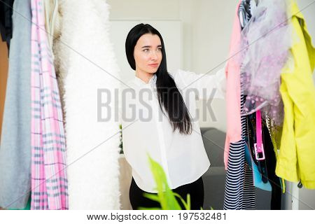 Frustrated young woman cannot decide what to wear