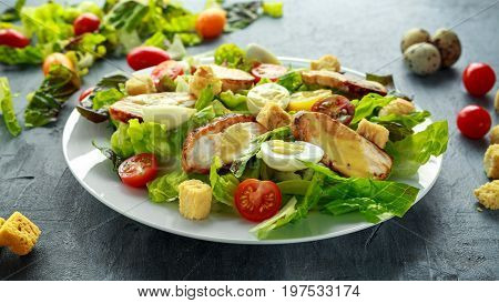 Fresh healthy Caesar salad with chicken, egg quail, tomatoes, Cheese and Croutons in a white plate.