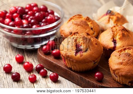muffins with cranberries cranberries in a glass bowl on the old wooden background