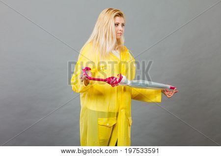Unhappy Woman Wearing Raincoat Holding Closed Umbrella