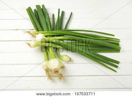 two bunches of spring onion on white wooden background