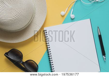 Blank Notebook With Sunglasses, Starfishes, Pencil, Earphone, On Yellow And Blue Background.