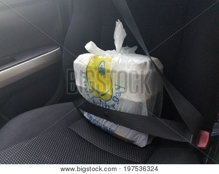 a takeout food bag and boxes wearing seatbelt in car