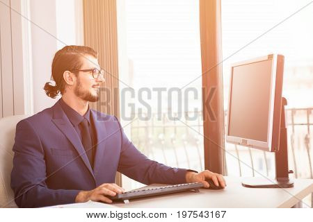 Manager in suit working at his computer next to a glass window. Image of successful anc competitive entrepreneur at his work place