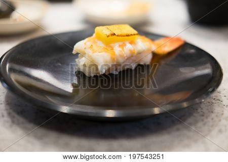 Close up of Ebi sushi with shrimp on a black diah