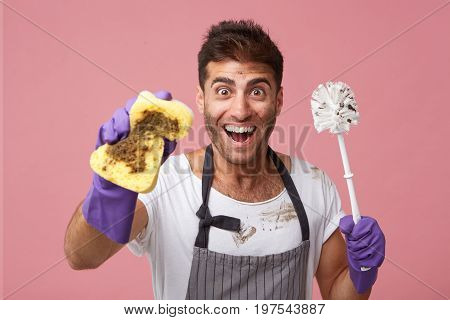Excited male worker wearing apron and protective gloves holding dirty sponge and detergent being untidy after cleaning bathroom looking with joyful expression directly into camera posing at studio
