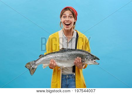Excited Fisherwoman Wearing Red Hat And Yellow Raincoat Holding Huge Fish In Hands Looking With Open