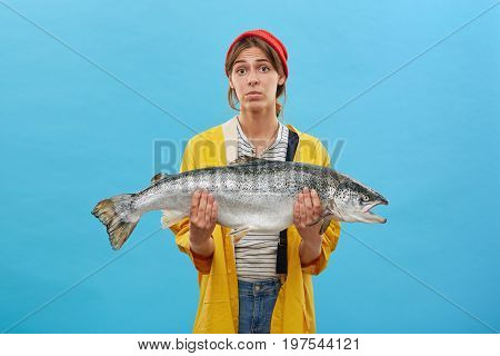 Beautiful Female Wearing Red Hat And Yellow Raincoat Selling Huge Fish Which She Catched At Lake Or