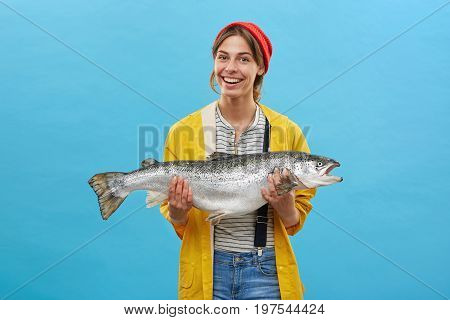 Horizontal Portrait Of Successful Female Angler Wearing Casual Clothes Holding In Hands Big Fish Hav