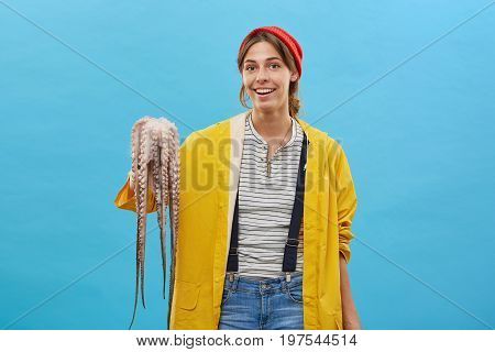 Portrait Of Attractive Young Fisherwoman Wearing Red Hat On Head And Yellow Raincoat Holding Octopus