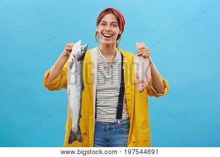 Indoor Shot Of Positive Young Fisherwoman Wearing Casual Clothes Returning From Fishing With Two Fis