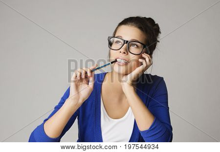 Thinking Business Woman Looking Up Pensive Young Girl in Glasses Dream over Gray Background
