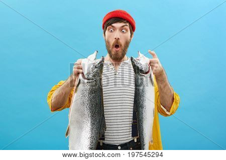 Portrait Of Blue-eyed Shocked Male Angler Looking With Bugged Eyes At Two Huge Salmons Being Surpris