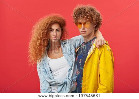 Stylish Hipster Couple Modeling In Studio. Beautiful Girl With Clean Freckled Skin And Ginger Volumi