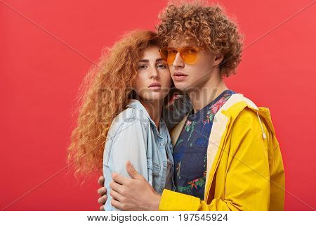 Street Fashion. Extraordinary Young European Hipster Couple Dressed In Trendy Clothes Posing Indoors