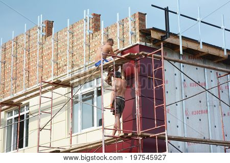 KYIV UKRAINE - AUGUST 16, 2017: Construction workers insulating house facade with mineral rock wool and siding installation. External wall insulation system (or EWIS) mineral wool for energy saving.