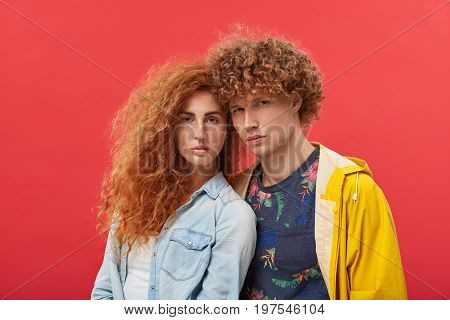 Portrait Of Lovely Woman With Well-shaped Eyebrows, Freckled Face And Ginger Curly Hair Standing Nea