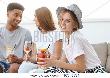 Portrait Of Youngsters Sitting Together At Cozy Sofa, Drinking Cocktails And Wine Having Party. Mixe