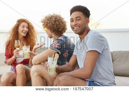 Cheerful Afro American Male With Dark Skin Sitting Near His Interlocutors And Friends Holding Lemon