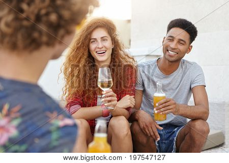 Portrait Of Three Friends Gathering Together To Discuss Their Party, Drinking Beer And White Wine Be
