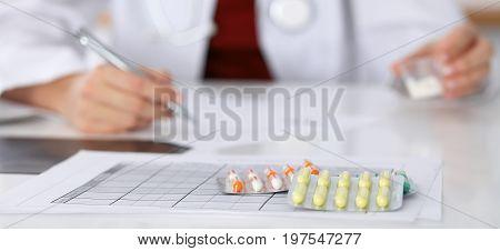 Female medicine doctor fills up prescription form to patient closeup.