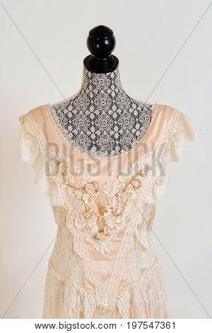 closeup vintage wedding dress with grey wall background
