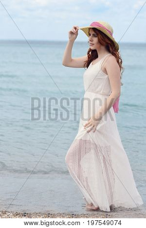 Woman walking in water at the beach wearing white dress