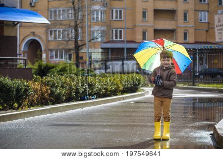 Little Boy Playing In Rainy Summer Park. Child With Colorful Rainbow Umbrella, Waterproof Coat And B