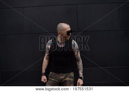 Confident serious young Caucasian bearded biker with mohawk and muscular tattooed arms posing outdoors at grey blank wall wearing stylish clothing and shades his whole look expressing confidence