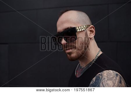 Close up outdoor portrait of handsome rock musician with stylish beard and mohawk looking at camera with serious and confident expression on his strong featured face going to rehearsal with his band