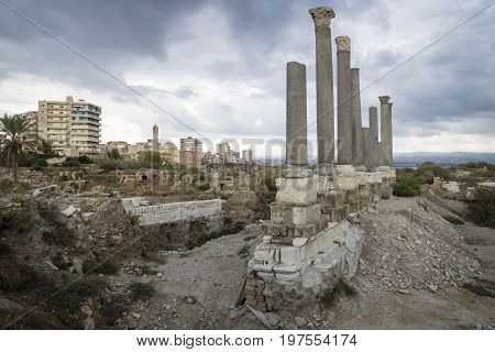 Pillars in the ruins with dark dramatic cloudscape with mosque in the cityscape of Tyre, Sour, Lebanon