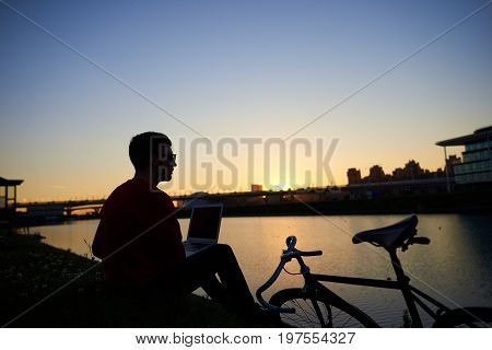 Silhoutte of hipster sitting on river bank with laptop pc on his lap admiring amazing sunset after he finished work feeling relaxed and connected to Universe. People modern lifestyle and technology
