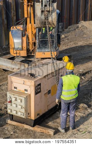 Workers Installing Electric Generator At Construction Site