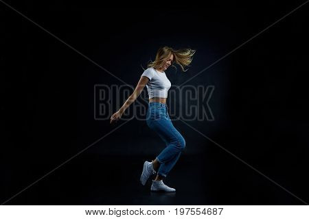 Full lenght studio shot of blonde European girl wearing crop top and blue stretch jeans stretching doing aerobics or dancing. People sports fitness dance energy flexibility and active lifestyle