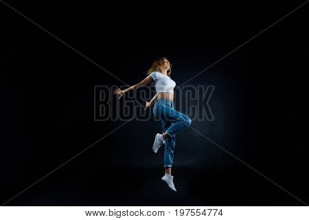 Studio shot of beautiful young European woman dancer with slim flexible body practising indoors sharpening her dancing skills dressed in sensible clothing. People hobby and active lifestyle concept