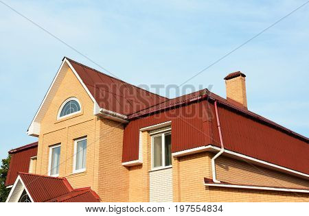 Mansard roof and roof gutter. Modern Brick House Facade Exterior. Modern House Construction. Hip and Valley roofing types.