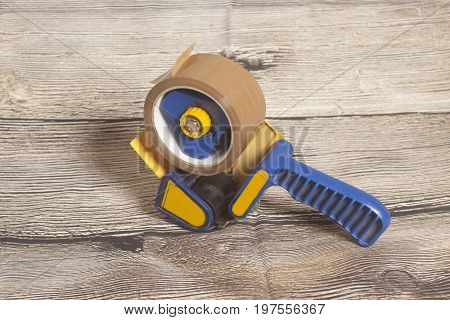 Industrial tape dispenser on a wooden background