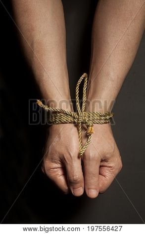 Male hands bound with rope on black background .